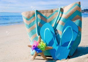 Beach bag with starfish and flip flops by the ocean